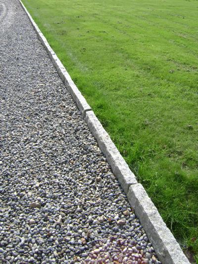 Adskild græs og grus med kantsten i granit