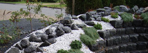 Havebed med granit- og marmorskærver opbygget med brosten